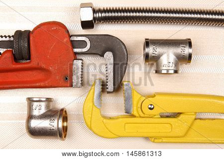 Set of plumbing and tools on the table. Fitting, grey suede gloves and two adjustable wrenches for plumbing works