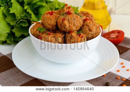 Meat balls with chilli and herbs in a white bowl closeup.