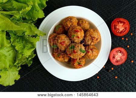 Meat balls with chilli and herbs in a white bowl on a black background. The top view.