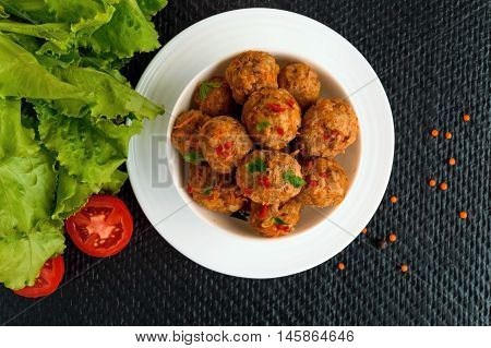 Meat balls with chilli and herbs in a white bowl. The top view