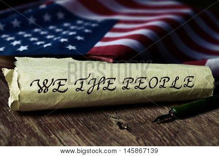 the text we the people, the first words of the United States Constitution, written with a dip pen in a yellowish piece of paper and the flag of the United States