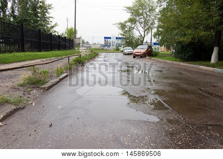 The pits on a bad road filled with rain water. On the side there are two (2) of the vehicle. In the background the blue building.