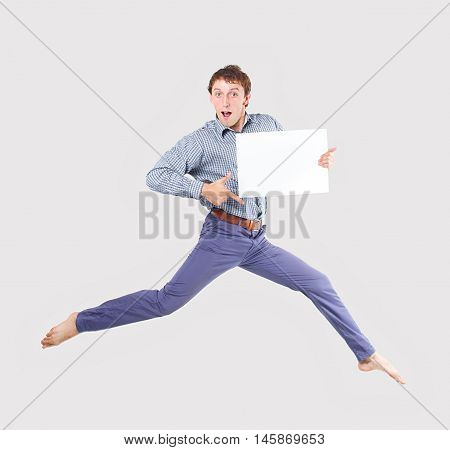 guy jumping and points to a white sheet of paper. surprised young man demonstrates an approving gesture and holding a blank sheet of white paper for your text. isolated on a gray background