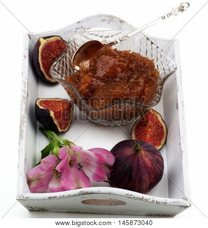 Delicious Homemade Fig Jam in Glass Kremanka with Fresh Fig Fruits and Flowers in White Wooden Tray isolated on White background