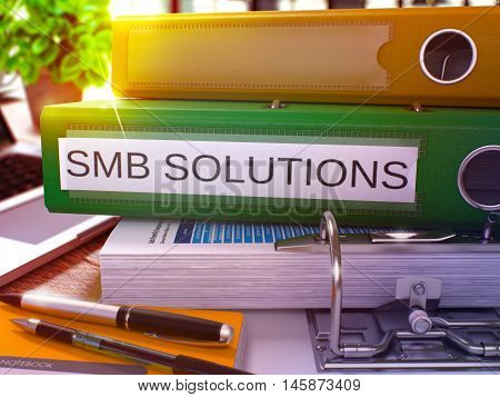 Green Office Folder with Inscription SMB - Small Business Solution - Solutions on Office Desktop with Office Supplies and Modern Laptop. SMB Solutions Business Concept on Blurred Background. 3D.