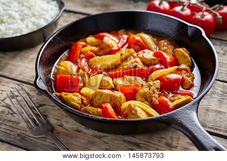 Chicken jalfrezi healthy traditional Indian culture restaurant curry spicy fried meat with chilli and vegetables, tomatoes, pepper, onion, asian food in cast iron pan on vintage table background