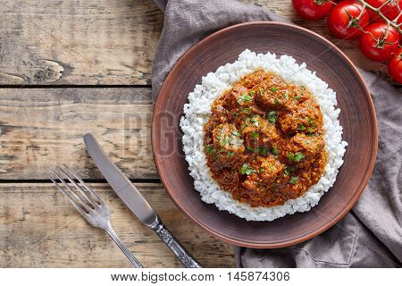 Madras butter Beef spicy asian garam masala slow cook lamb food with rice and tomatoes in clay plate on vintage wooden table background. Delicious India culture restaurant dish.