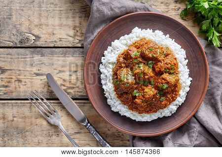 Madras butter Beef spicy Indian garam masala slow cook lamb food with rice and tomatoes in clay plate on vintage wooden table background. Delicious India culture restaurant dish.