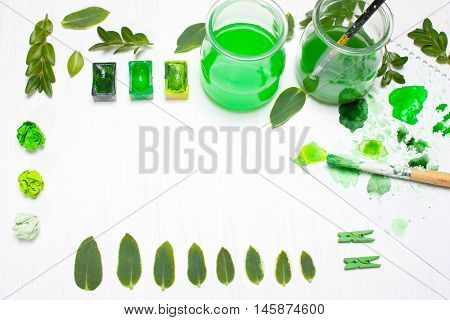 Green leaves draws the artist. Concept art.Ccreative concept creativity.Workplace designer table.Flat lay overhead view