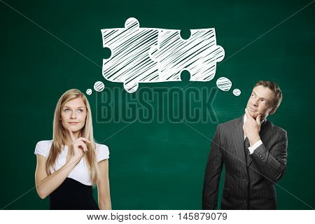 Attractive businessman and businesswoman thinking about puzzle pieces on blackboard background. Teamwork and partnership concept