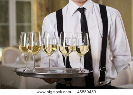 white wine glasses on a tray waiter tray with white wine a lot of glasses