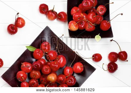 Two Black Wooden Plates with Fresh Ripe Sweet Maraschino Cherries closeup on Plank White background. Top View