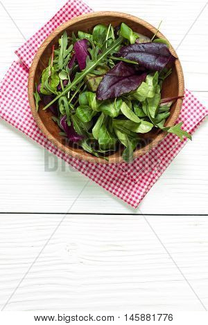 Fresh green salad with spinach ruccola lettuce on wooden table.