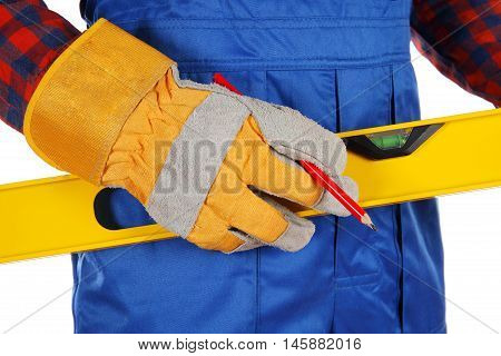 Worker man holding yellow spirit level and red pencil isolated on over white background