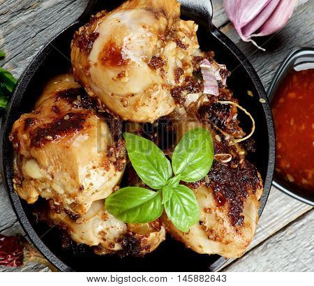 Delicious Spicy Roasted Chicken Legs with Herbs Sauce and Spices in Black Frying Pan on Rustic Wooden background. Top View