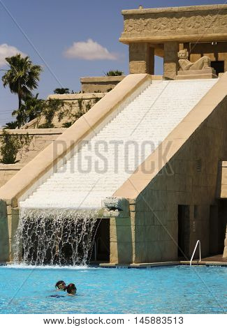 LAS VEGAS, NEVADA, MAY 23. The Cancun Resort on May 23, 2016, in Las Vegas, Nevada. A pair of bathers enjoys the dramatic Mayan waterscape and pyramid at the Cancun Resort in Las Vegas Nevada.