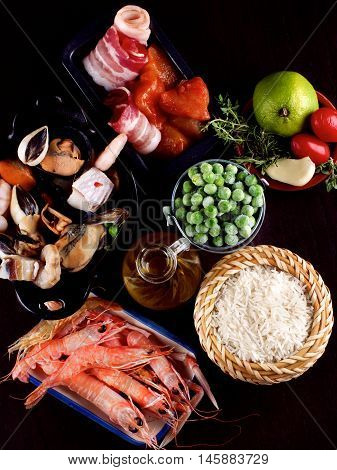 Arrangement of Raw Ingredients of Spanish Traditional Paella with Various Seafood Mussels Vegetables Rice and Olive Oil closeup on Dark Wooden background. Top View
