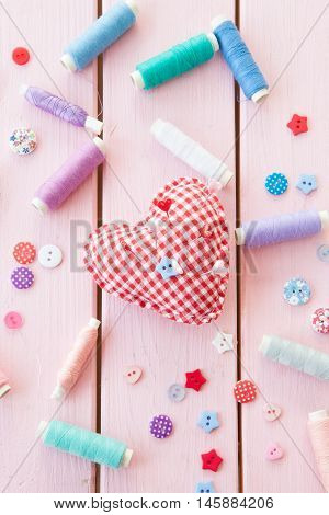 Pincushion in a heart shape and colorful yarns on pink