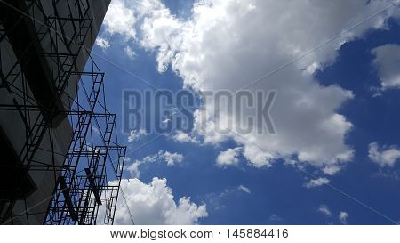 Scaffolding as safety equipment on a construction site with blue sky background. Daylight.