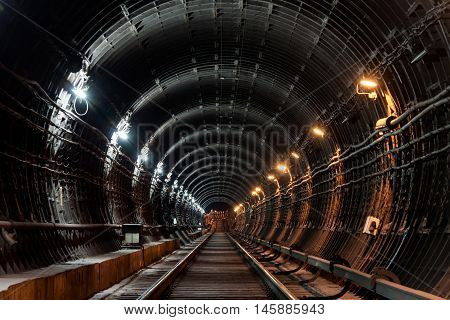 Straight circular subway tunnel with tubing and two different lights: white and yellow.