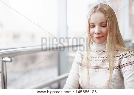 portrait of pretty blonde girl. beautiful girl smiles shyly and hides the eyes. empty space for your text
