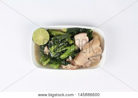 Fried Chinese kale and streamed streaky pork in soup on white background.