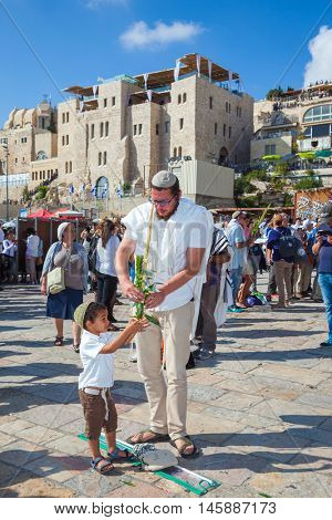 JERUSALEM, ISRAEL - OCTOBER 12, 2014:  The area in front of Western Wall of Temple filled with people.  Morning autumn Sukkot, Blessing of the Kohanim. The Jews of ritual clothes - tallit.