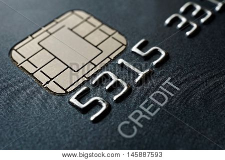 Macro detail of a brand new black and gray luxurious credit card with focus on the caption Credit, metal electronic chip and embossed numbers and letters