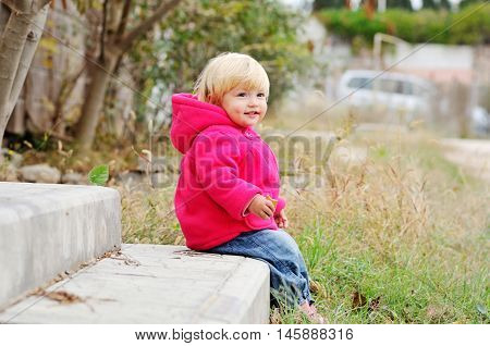 baby girl eating cake and sitting on the threshold