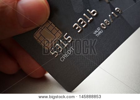 Male hand holding a brand new black and gray luxurious credit card with focus on the caption Credit, metal electronic chip and embossed numbers and letters
