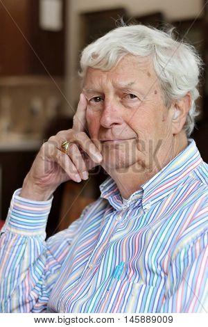 Portrait of a senior gentleman wearing hearing aids, age 78.