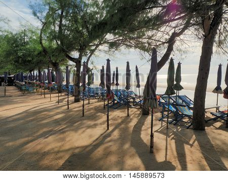 Beach chairs and umbrellas with sunny light for tourism relax in vocation at Cha-Am beach Thailand