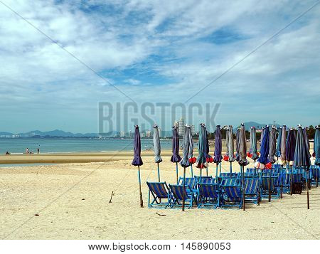 Colorful beach chairs and umbrellas for tourism relax in vocation at Cha-Am beach Thailand