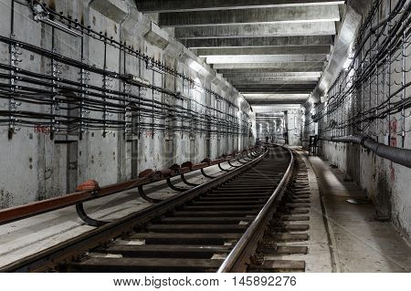 rectangular subway tunnel with a turn to the left and white lighting.