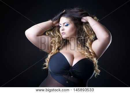 Young beautiful caucasian plus size model with big breast in black bra xxl woman on dark background professional makeup and hairstyle