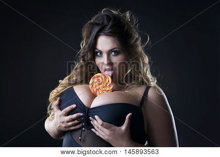 Young beautiful caucasian plus size model with big breast in black bra licking a lollipop xxl woman on dark background professional makeup and hairstyle