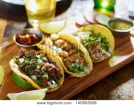 three different mexican street tacos with beef and pork