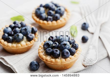 Tartlets with blueberries bilberry ricotta and honey syrup on vintage background. Delicious dessert.
