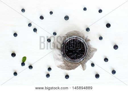 flat layout with blueberry berries strewn around the open the jar berry jam top view / jam appetizing berry