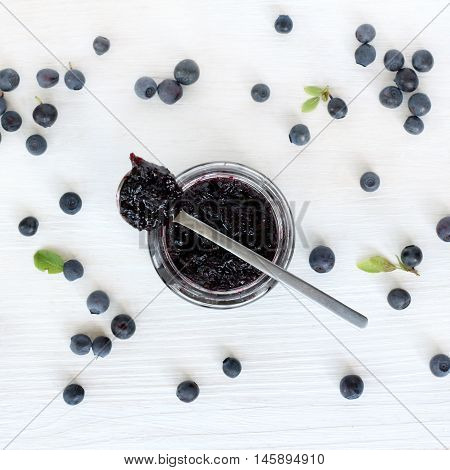 flat layout with blueberry berries strewn around the open the jar berry jam on a light wooden surface top view / spoon of jam for breakfast