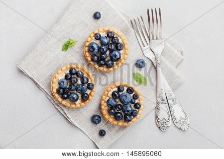 Tartlets with blueberries bilberry ricotta and honey syrup on vintage background from above. Delicious dessert. Flat lay styling.