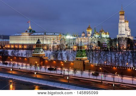 Winter night view of the Moskva River and Moscow Kremlin, where the Grand Kremlin Palace, Assumption Belfry with Gostunskii Nicholas Cathedral, the Archangel Cathedral and the Annunciation Cathedral.