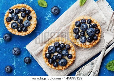 Tartlets with blueberries bilberry ricotta and honey syrup on vintage background top view. Delicious dessert. Flat lay styling.