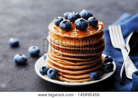 Stack of baked american pancakes or fritters with blueberries and honey syrup on rustic black table. Delicious dessert for breakfast.