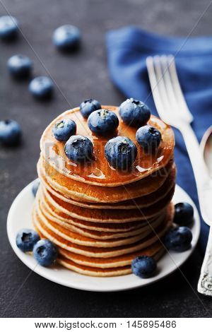 Stack of baked american pancakes or fritters with blueberries and honey syrup on vintage black table. Delicious dessert for breakfast.