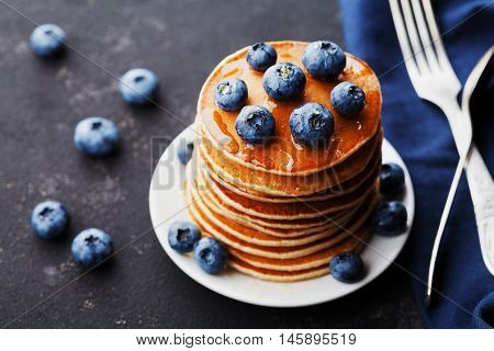 Stack of baked american pancakes or fritters with blueberries and honey syrup on rustic black background. Delicious dessert for breakfast.