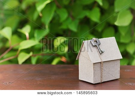 Model of cardboard house with key against green leaves background. Purchase rent and construction country real estate concept.
