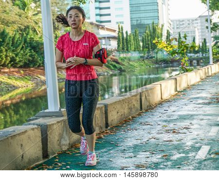 Kota Kinabalu,Sabah-Aug 31,2016:Malaysian joggers run past a calm morning view of Lagoon at Sutera Harbour Resort,Kota Kinabalu,Sabah,Borneo on 31st Aug 2016