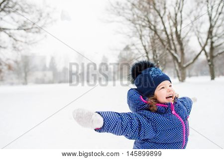 Cute little girl in blue jacket and knitted hat playing outside in winter nature, arms stretched