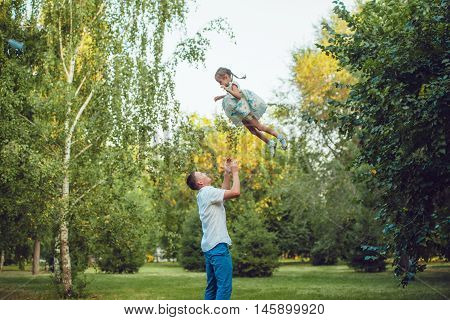 Father throws up his daughter in a park